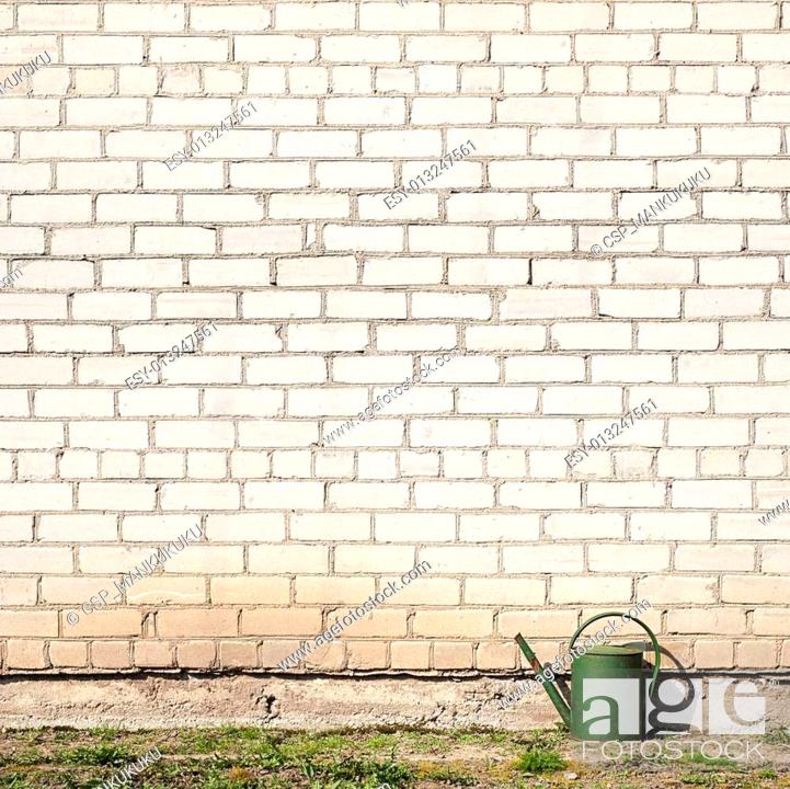 Stock Photo: watering can near the wall.