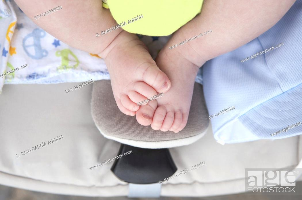 Stock Photo: Newborn baby chubby feet over on i-size baby car over pushchair. Overhead shot.