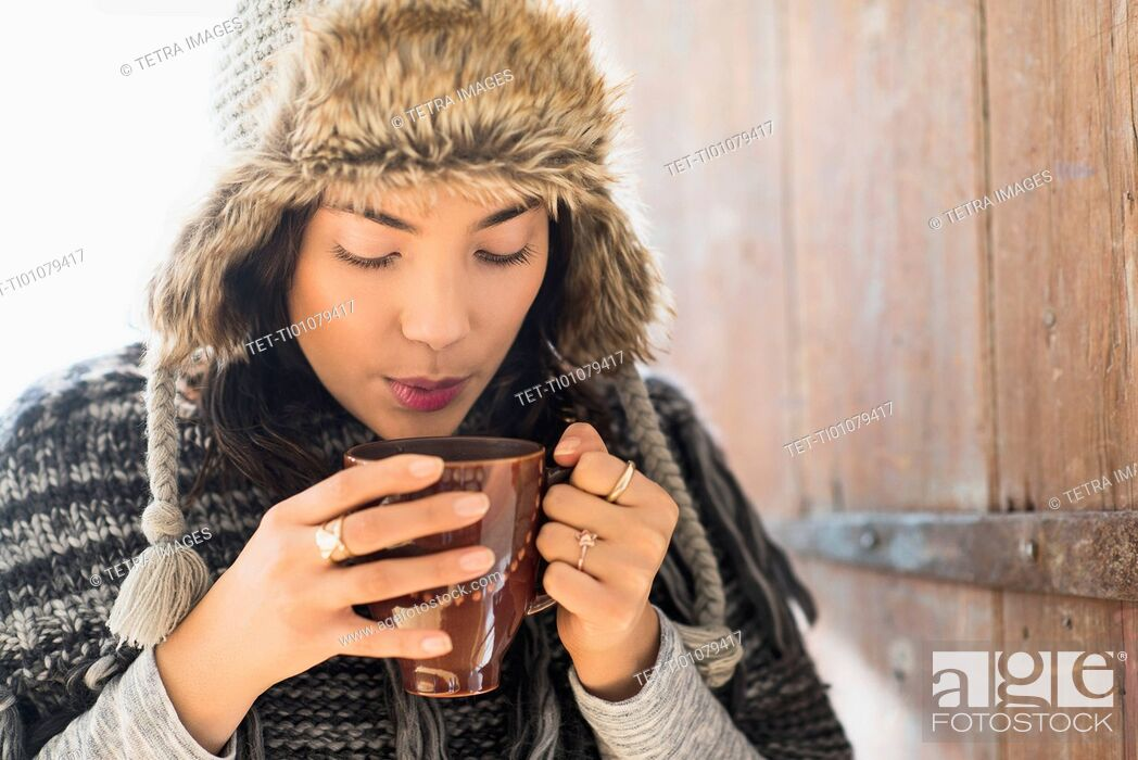 Stock Photo: Portrait of young woman wearing warm hat, blowing on cup of drink.