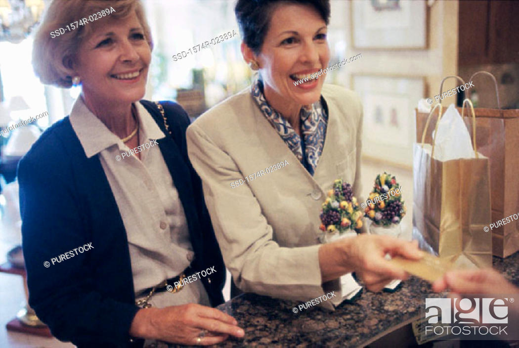 Stock Photo: Two mature women at a store counter.