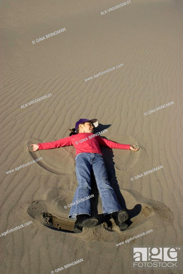 Young Girl Making A Snow Angel On A Sand Dune At Bruneau Dunes State