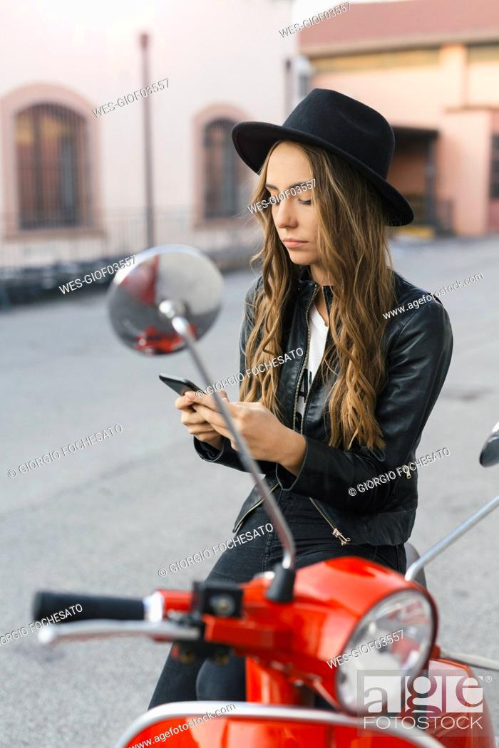 Stock Photo: Portrait of fashionable young woman with red motor scooter using cell phone.
