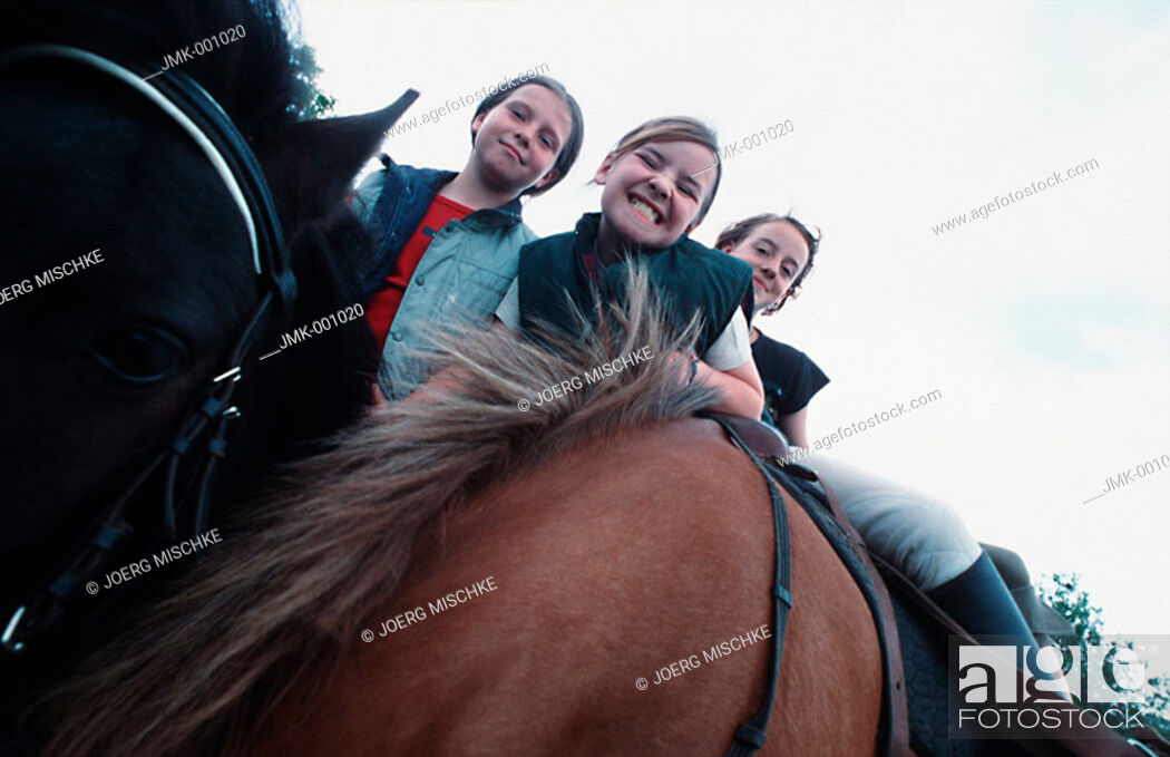Stock Photo: Three girls riding horses, sitting in the saddle, smiling.