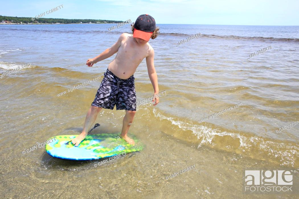 Stock Photo: A 7 year old boy standing on a surf board in the waves at a beach at the sea.