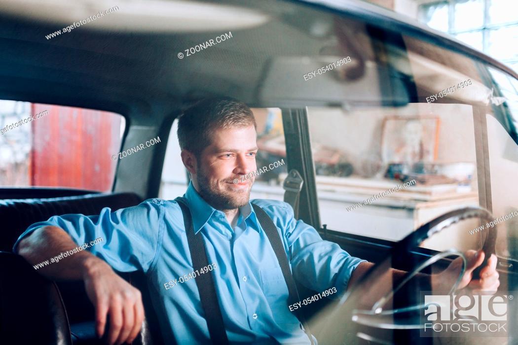 Stock Photo: Handsome man sitting inside his old vintage car.