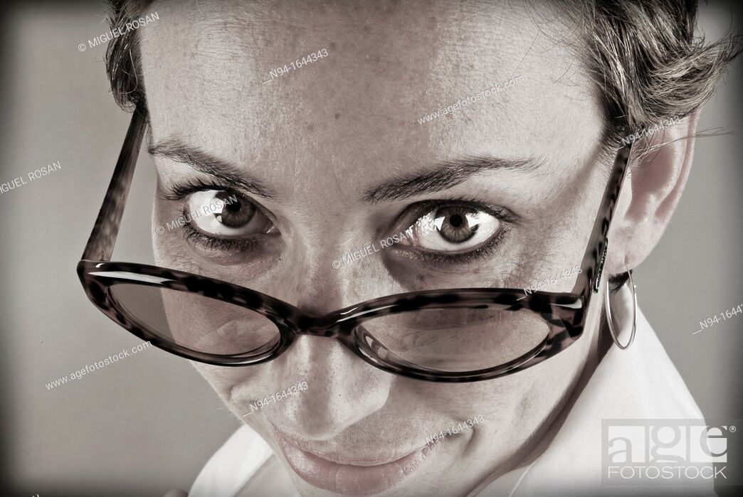 Stock Photo: Closeup of young woman staring at the camera above his glasses.