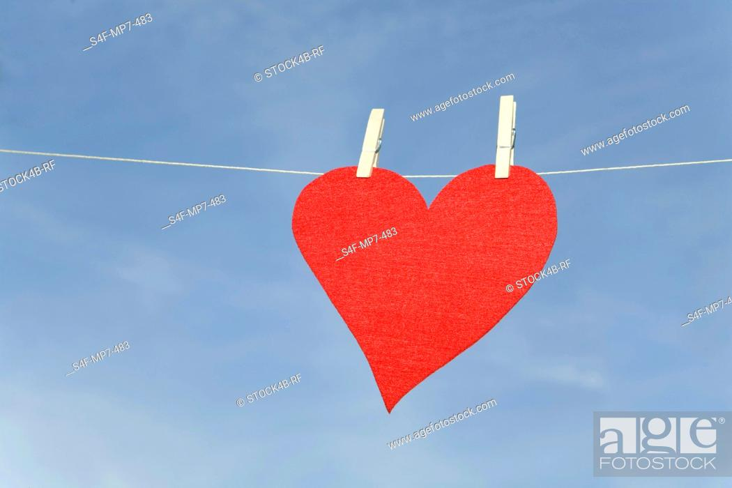 Stock Photo: Red heart hanging on clothesline.
