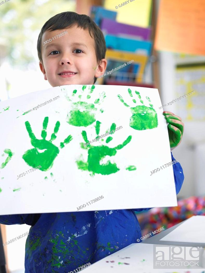Stock Photo: Boy presenting his finger painting in art class.