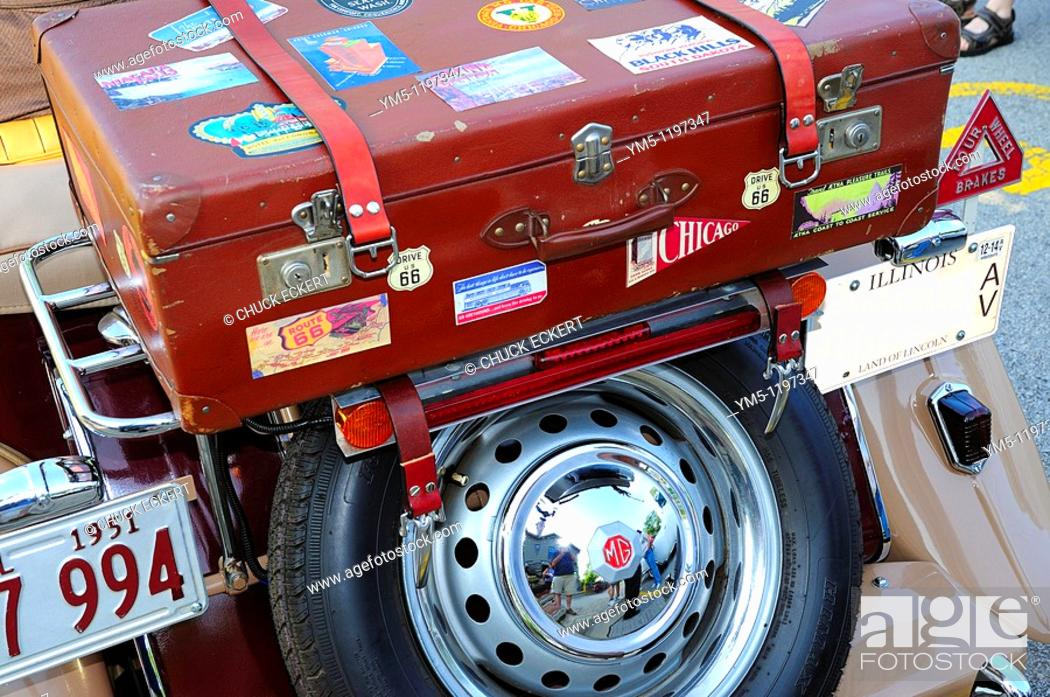 Stock Photo: 1951 MG TD Convertible with rear luggage rack & suitcase with travel stickers.