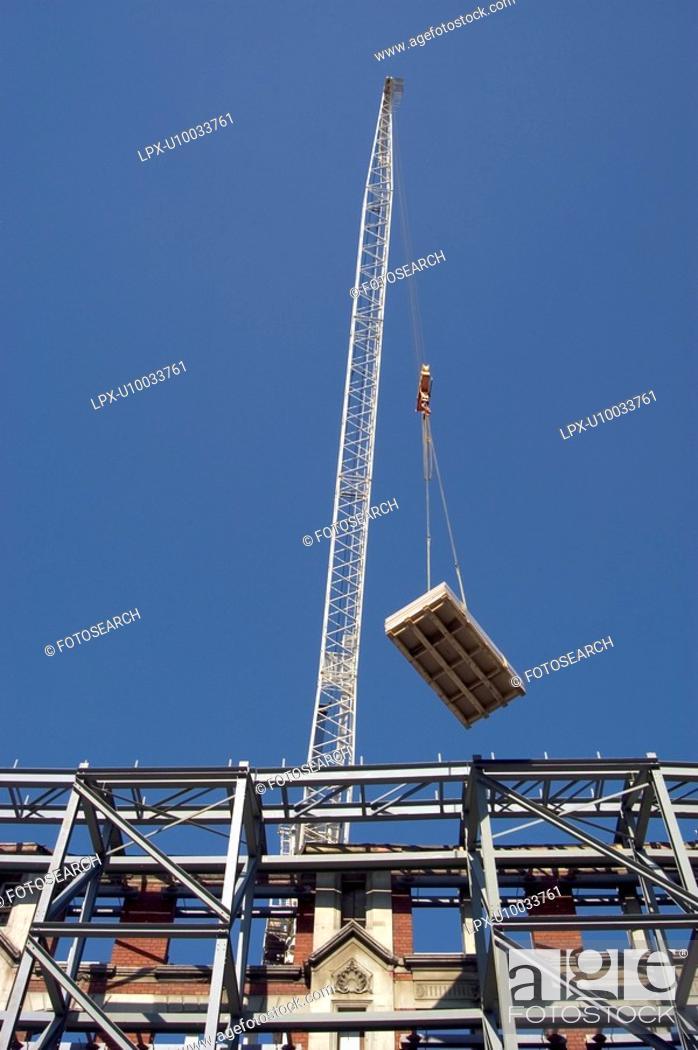 Stock Photo: Facade Retention. Crane lifting construction material.