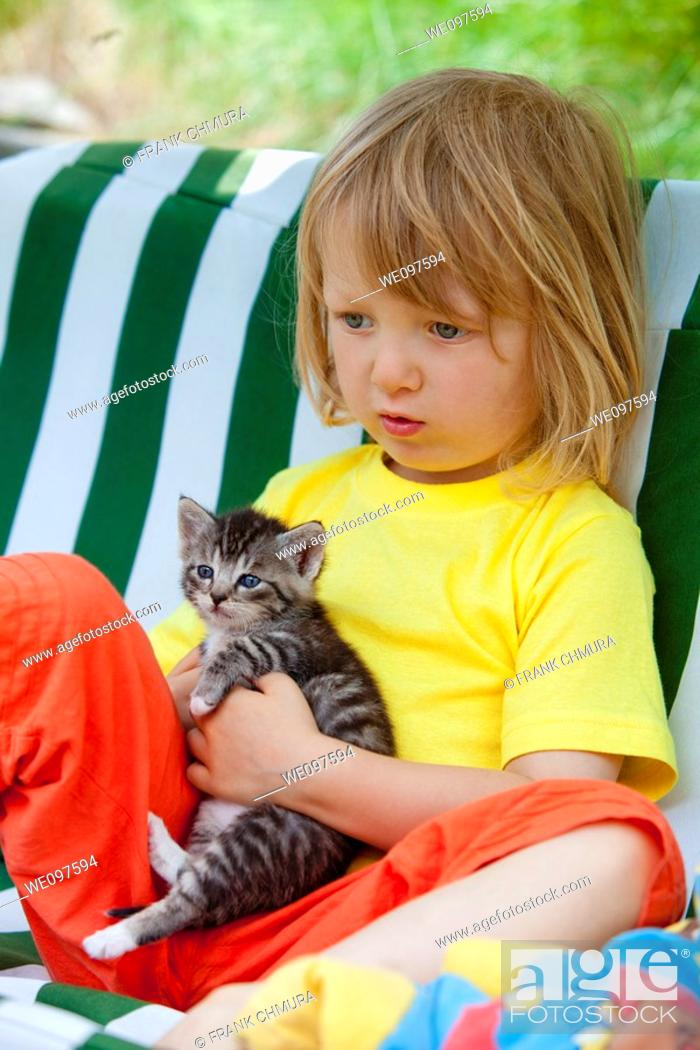Stock Photo: blond boy playing with kitten.