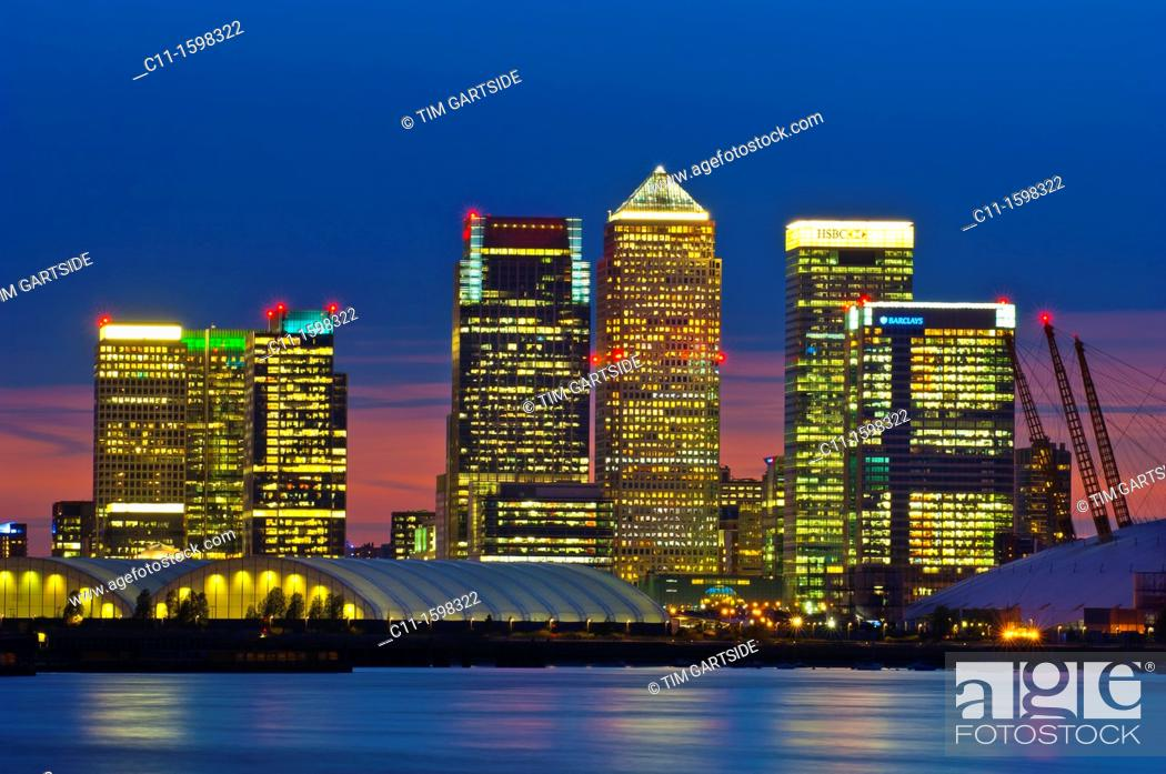 Stock Photo: canary wharf skyline shot from across the river thames at night.