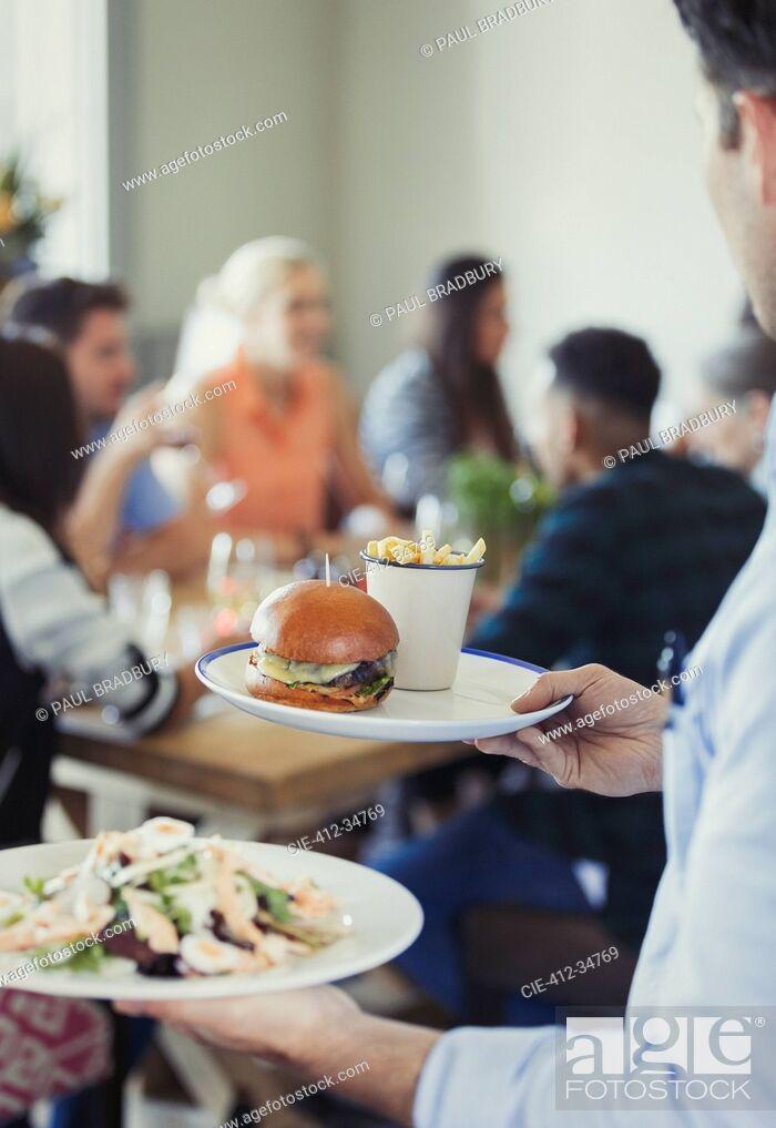 Stock Photo: Waiter serving food in restaurant.
