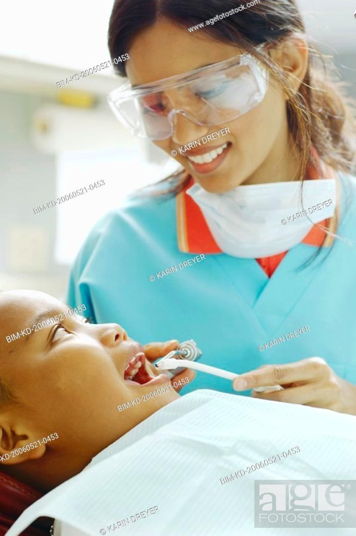 Stock Photo: Indian female dental assistant working on African boy.