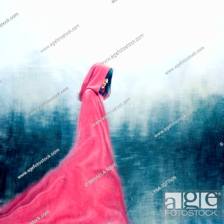Stock Photo: Woman wearing red cloak walking outdoors.