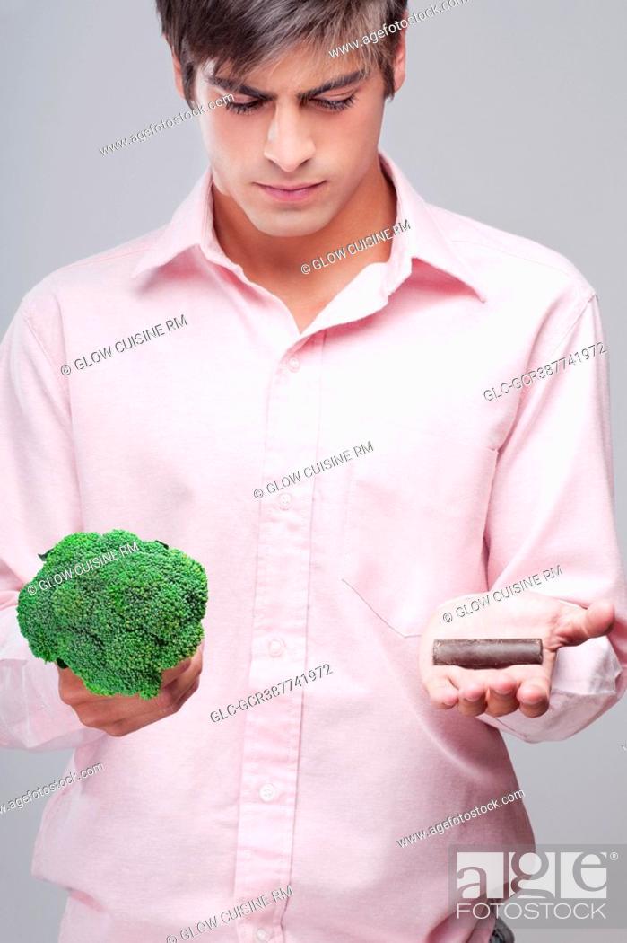 Stock Photo: Man choosing between broccoli and chocolate.