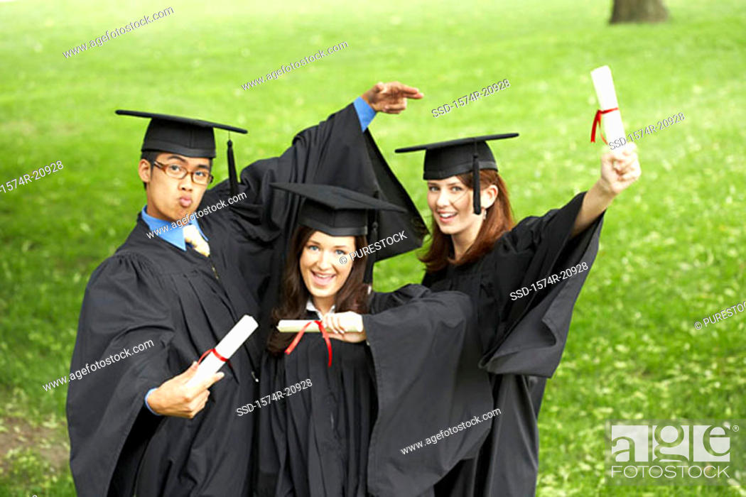Stock Photo: Portrait of two female graduates and a male graduate holding diplomas.