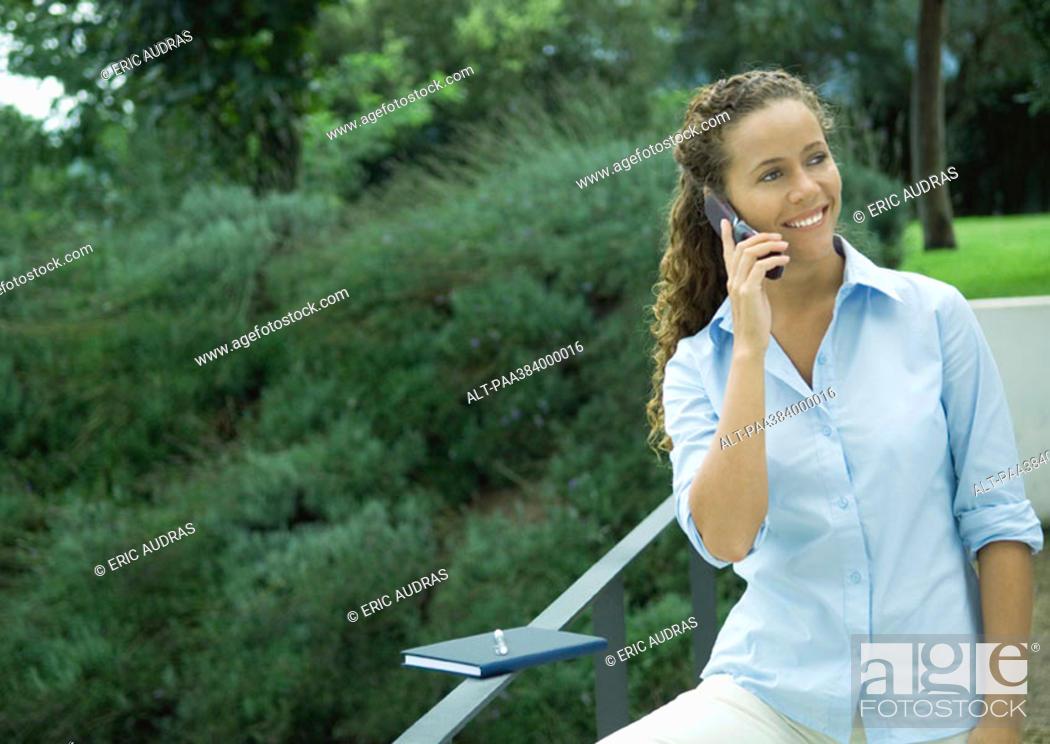 Stock Photo: Woman using cell phone outdoors, agenda balanced on railing.