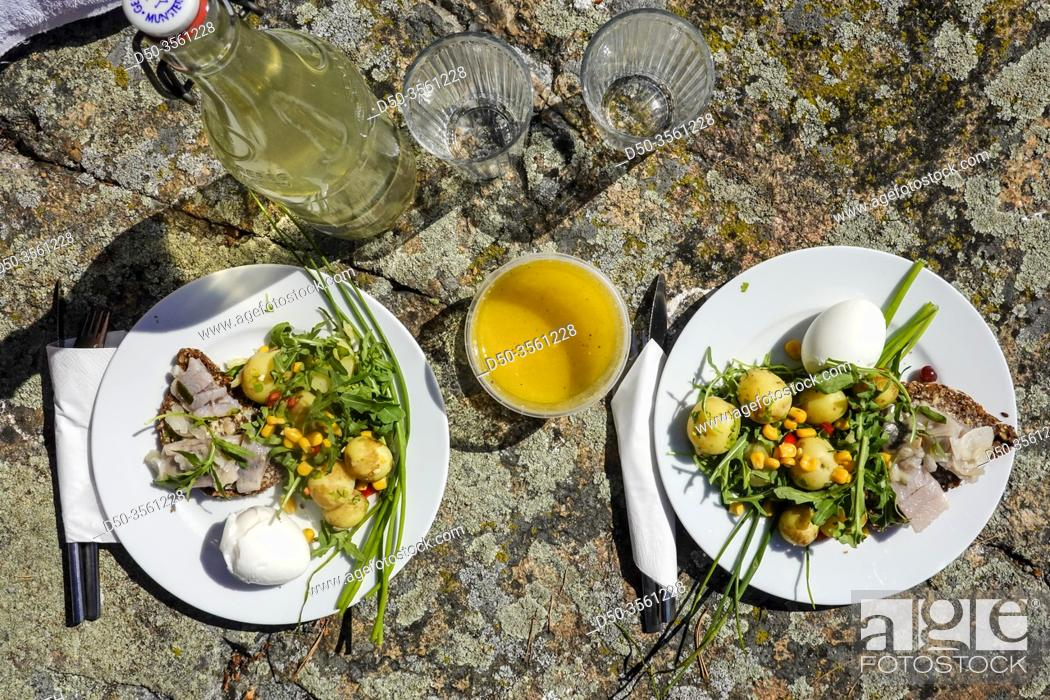Imagen: Two plates with midsummer delicacies like potato salad, herring and dark bread.