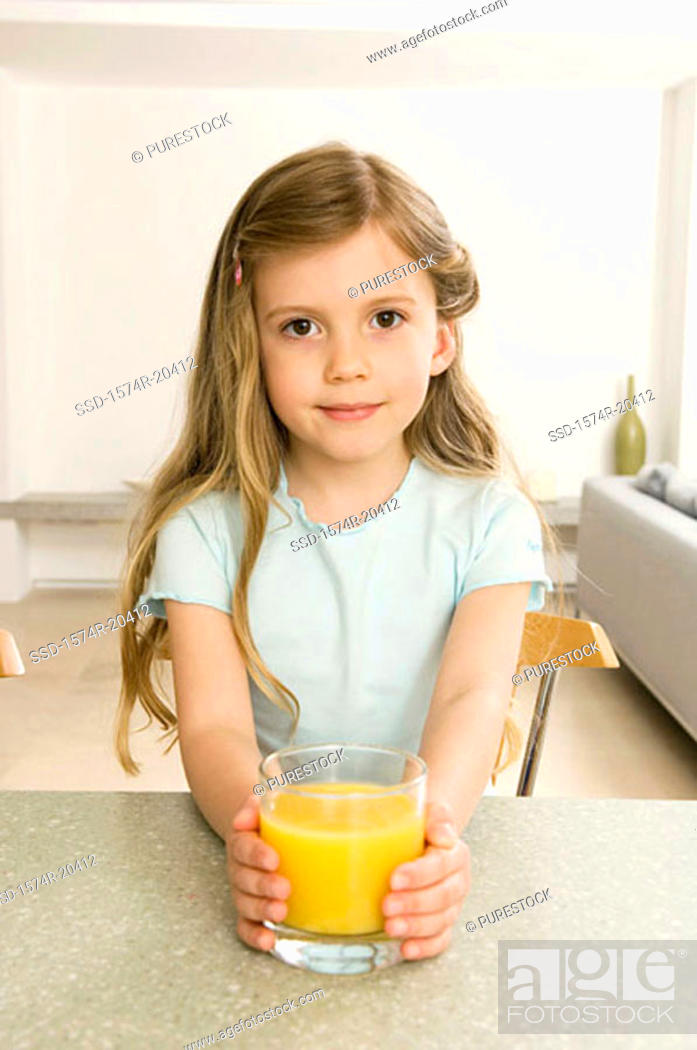 Stock Photo: Portrait of a girl holding a glass of orange juice.