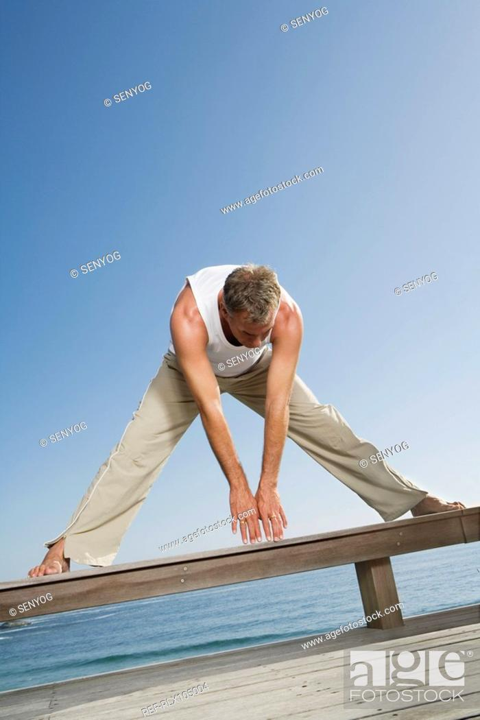 Stock Photo: Mature man doing fitness exercises on wooden bench with ocean in background.