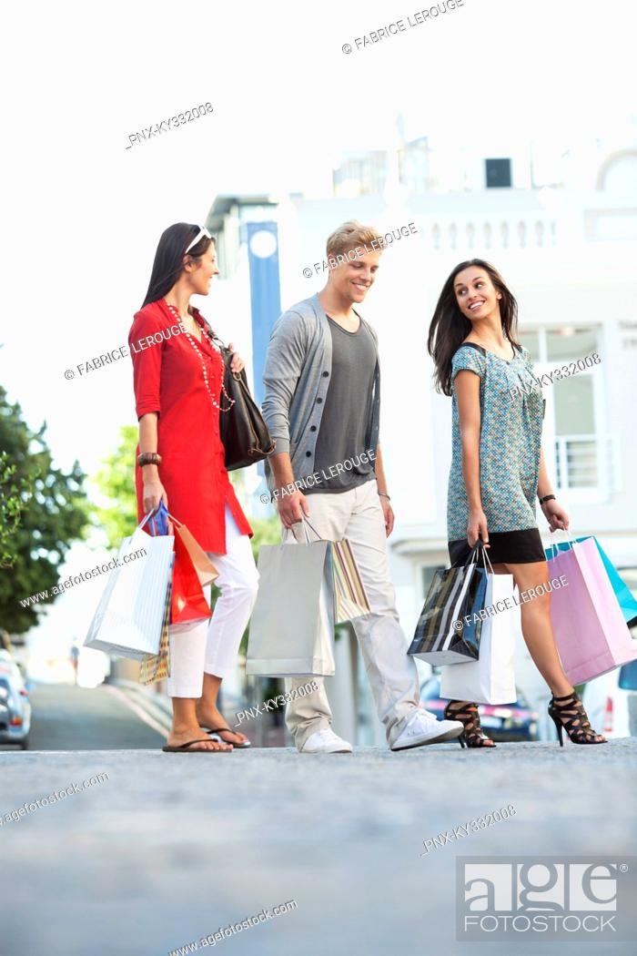 Stock Photo: Young man with two women walking with shopping bags.