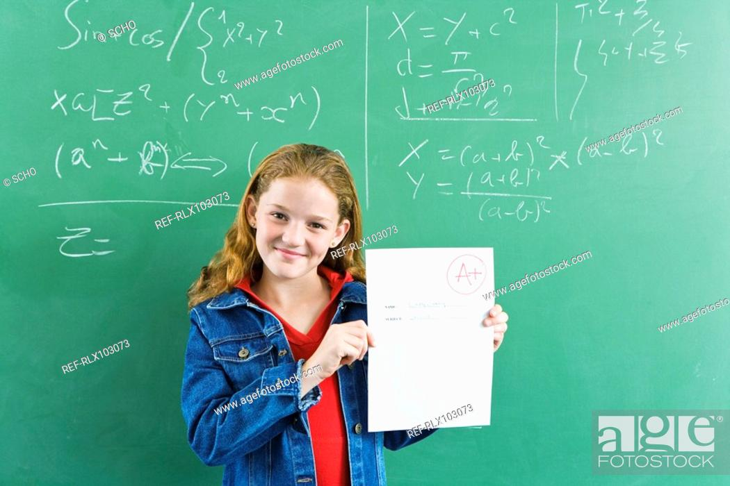 Stock Photo: Girl 10-13 holding up test paper with A+ mark on it, in front of blackboard.