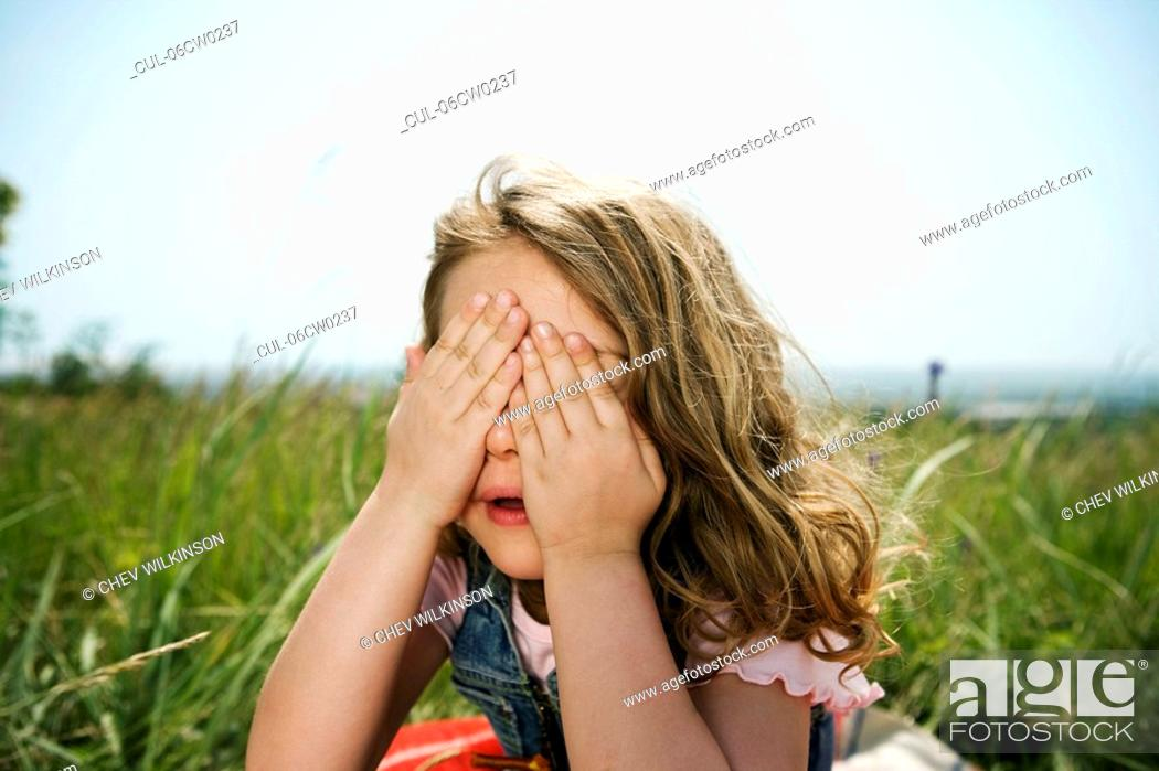 Stock Photo: Girl hiding behind hands.