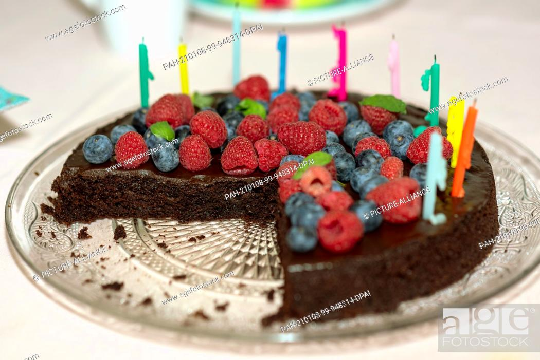 Stock Photo: 12 December 2020, Saxony-Anhalt, Magdeburg: On a table is a chocolate birthday cake with raspberries, blueberries and ten candles.