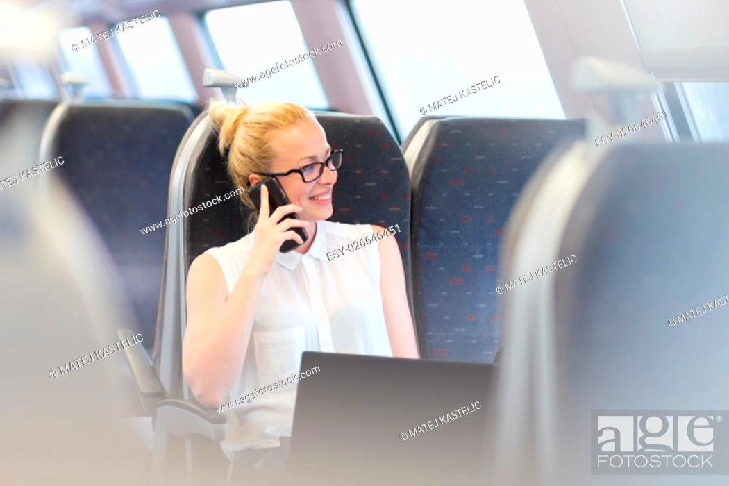 Stock Photo: Businesswoman talking on cellphone and working on laptop while traveling by train. Business travel concept.