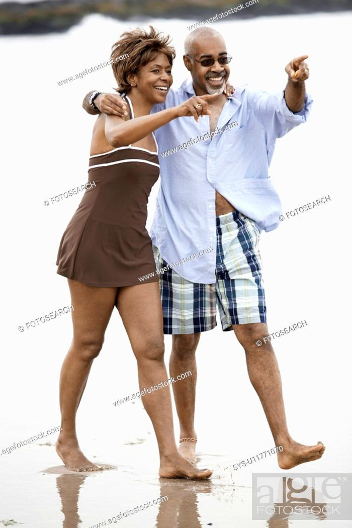 Stock Photo: Couple walking and pointing at beach.