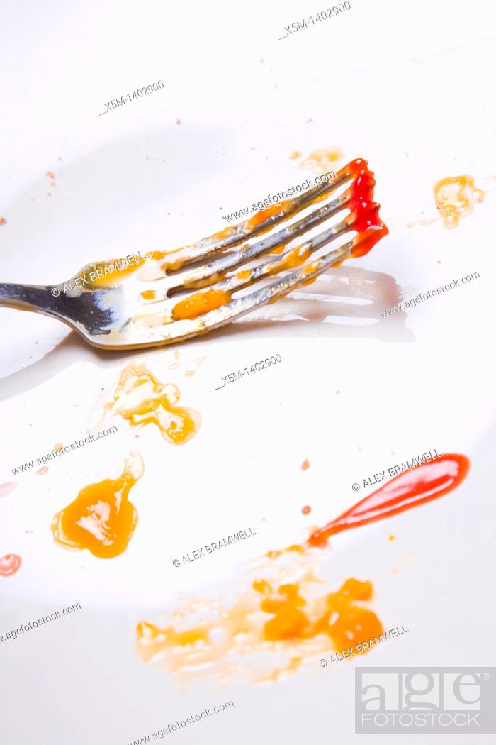 Stock Photo: Fork on a plate with crumbs and splatters of ketchuop and egg yolk.