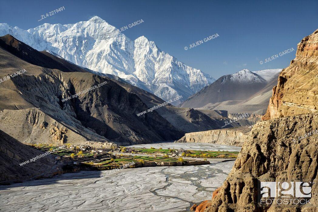 Stock Photo: The village of Chuksang (2900m) surrounded by fields in the valley of the Kali Gandaki river, Nilgiri peak (7061m). Nepal, Gandaki.