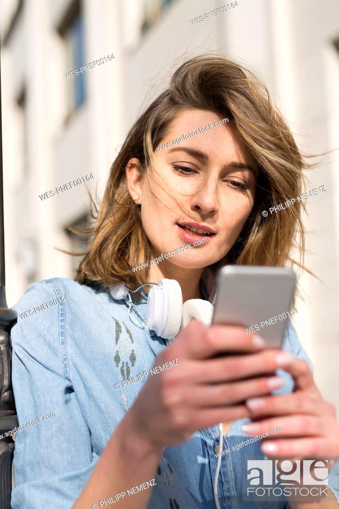 Stock Photo: Portrait of woman with headphones looking at cell phone.