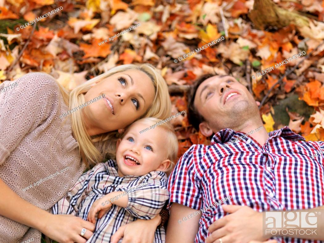Stock Photo: Happy smiling young parents and a two year old girl lying on colorful fallen tree leaves in autumn nature.