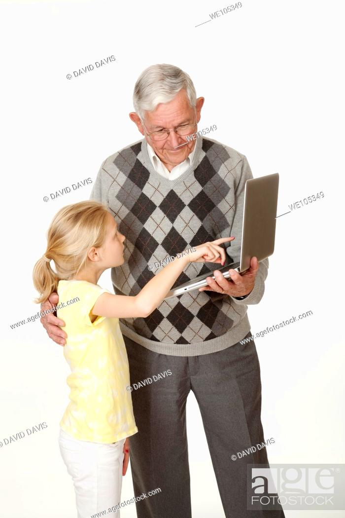 Stock Photo: Cute Caucasian granddaughter showing her grandfather something on the computer.