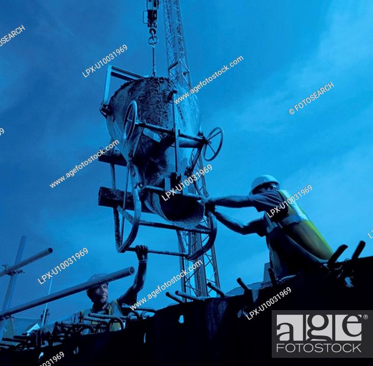 Stock Photo: Workers positioning hopper before placing concrete to reinforced structure.