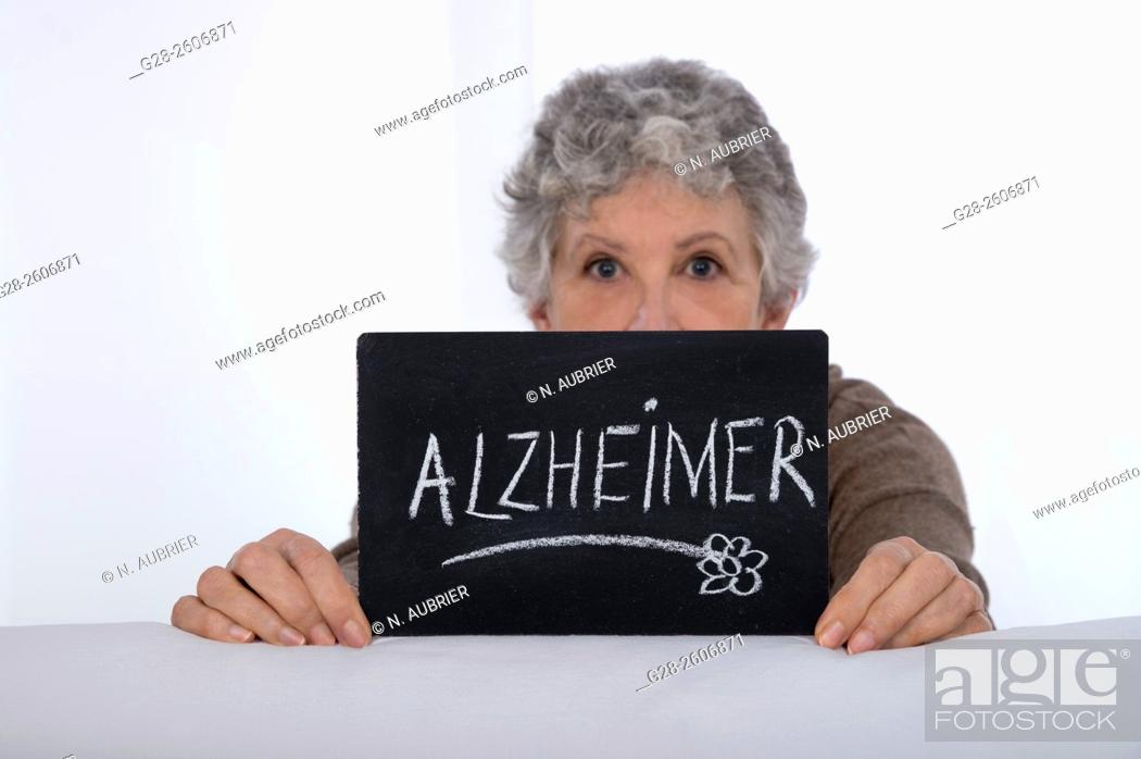 Stock Photo: Senior Woman with grey hair holding a black slate with Alzheimer written on it.