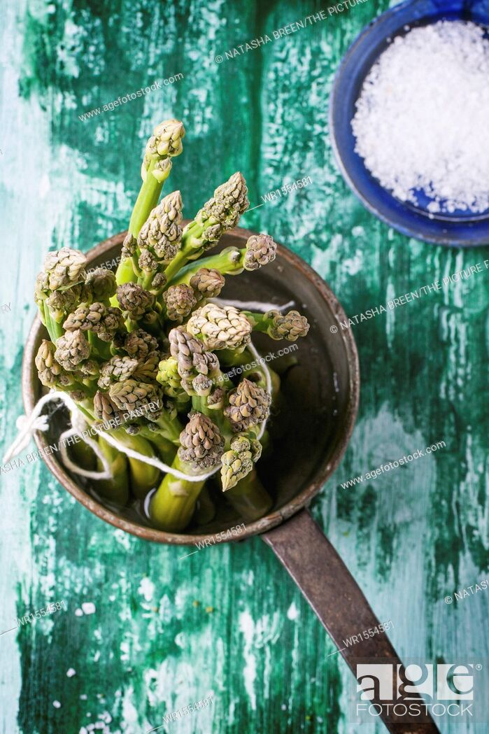 Stock Photo: Bunch of young green asparagus in vintage pot over green wooden table. Top view.