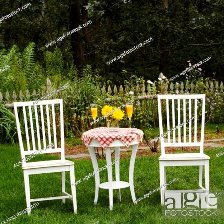 Stock Photo: Two chairs and a table in a garden.