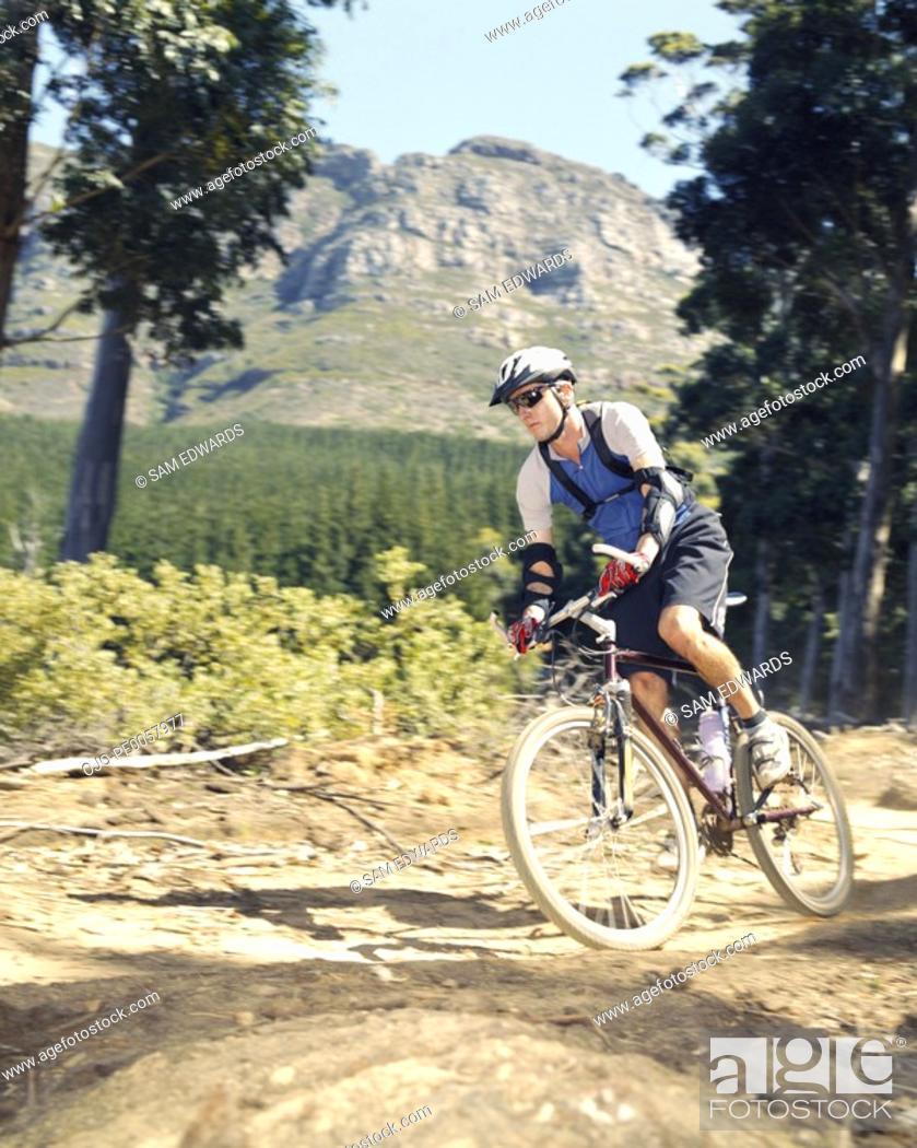 Stock Photo: A man mountain biking on a trail.
