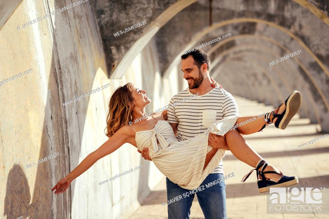 Stock Photo: Spain, Andalusia, Malaga, happy man carrying girlfriend under an archway in the city.