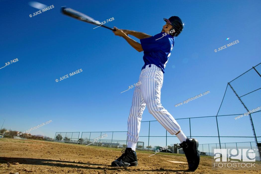 Stock Photo: Baseball batter, in blue uniform, hitting ball during competitive game, side view surface level, blurred motion.