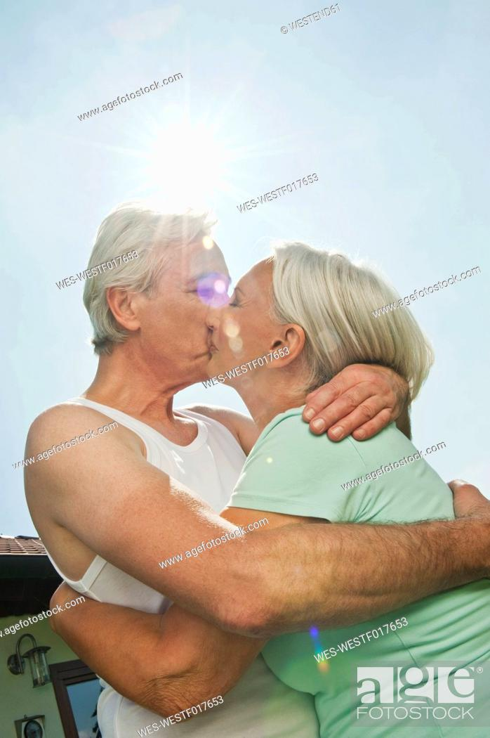 Stock Photo: Germany, Bavaria, Man and woman kissing each other against sky, smiling.