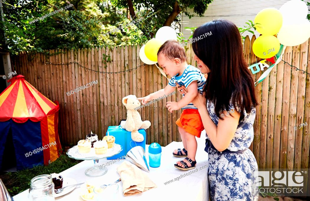 Imagen: Mother holding baby boy on table, pointing to soft toy.
