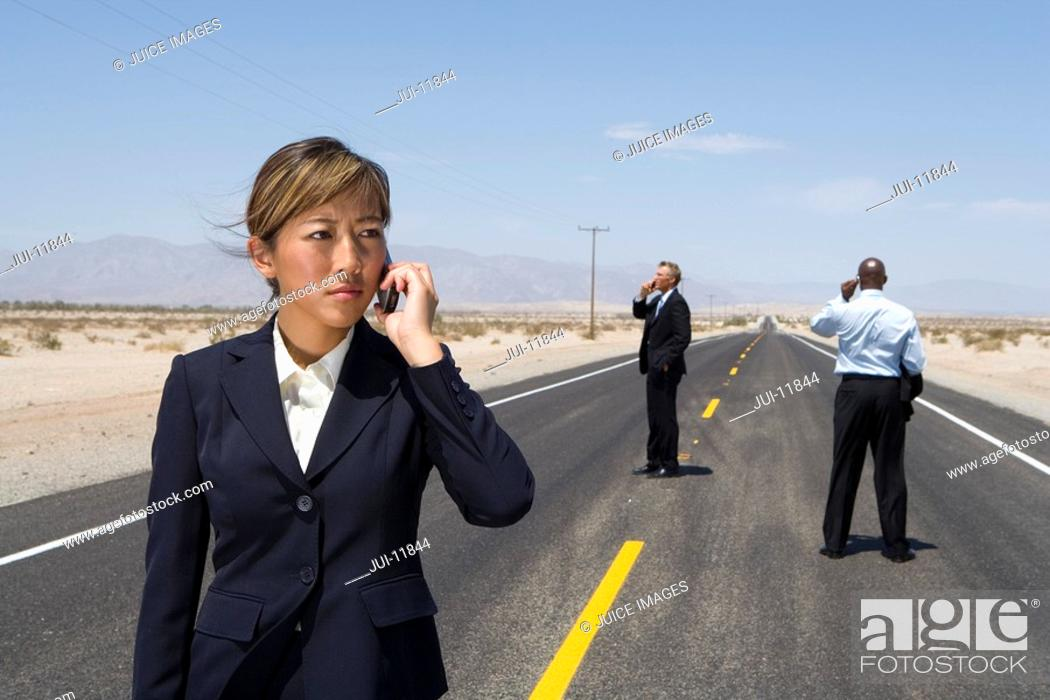 Stock Photo: Businessmen and woman in middle of desert road using mobile phones.
