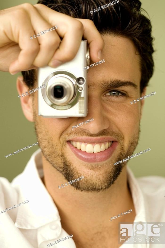 Stock Photo: Portrait of a young man taking pictures.