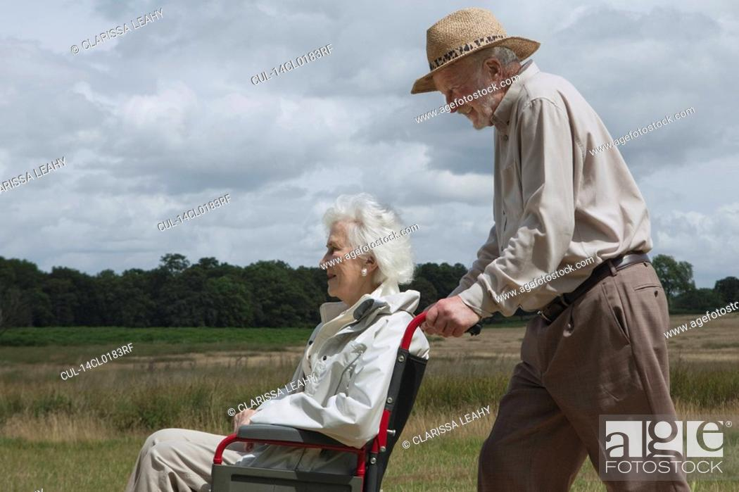 Stock Photo: Elderly man pushing woman in wheelchair.