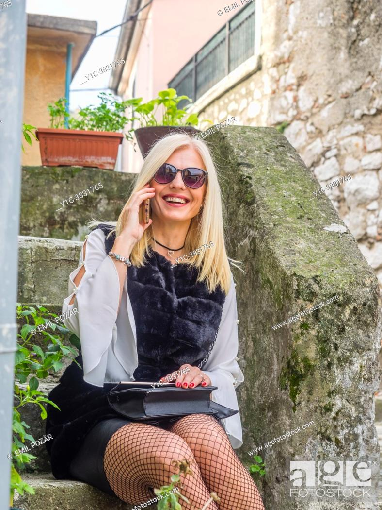 Stock Photo: Pretty mature blonde woman is sitting outside and talk on smartphone.