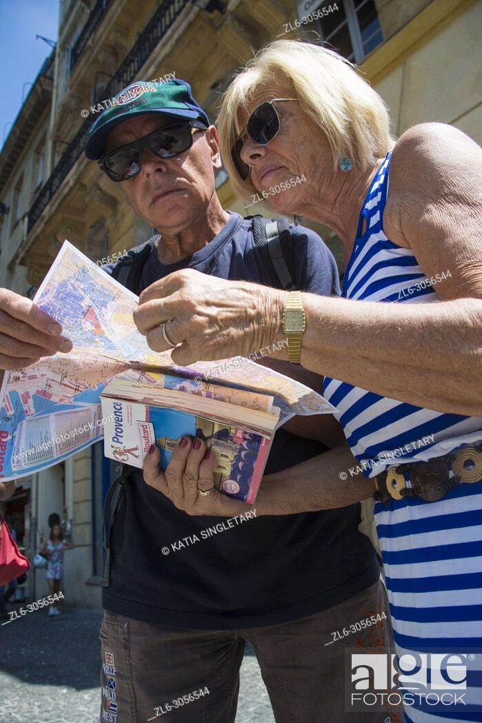 Stock Photo: Older mature retired couple looking at a map trying to figure out their way in the streets of the city of Marseille.